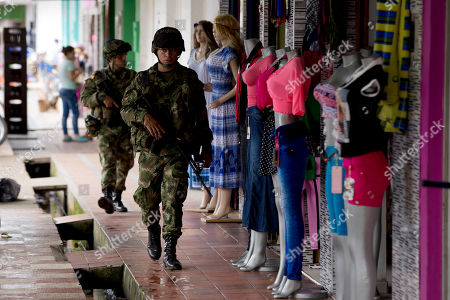 Soldiers patrol in Puerto Rico, southern Colombia. Puerto Rico sits one town away from a vast, desolate savannah known as Yari Plains where leaders of the Revolutionary Armed Forces of Colombia, FARC, have been gathering this week for their final conference as a guerrilla army. The town has long been a guerrilla stronghold and base of operations for one of the FARC's most-feared units, the Teofilo Forero mobile column, which attacked Puerto Rico's city council killing four of it members, kidnapped former presidential candidate Ingrid Betancourt, and bombed an elite social club in Bogota that left 36 dead