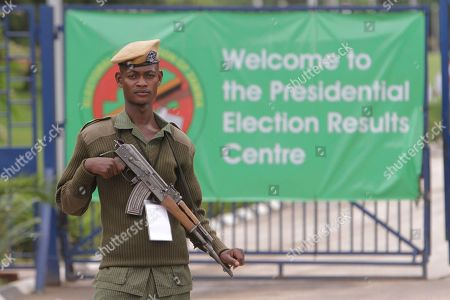 An armed police officer stands guard outside the presidential election results center following demonstrations by supporters of presidential candidate Hakainde Hichilema, a day after presidential elections in Lusaka, Zambia Wednesday, Jan, 21, 2015. Candidates vying to replace Zambia's late President Michael Sata have cast their ballots along with thousands of other voters in Tuesday's presidential election