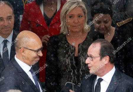 French President Francois Hollande, right, speaks with Deputy Minister for European Affairs Harlem Desir during a ceremony in which he acknowledged the state's responsibility in abandoning Algerians who fought alongside French colonial forces in Algeria's war for independence, at the Hotel des Invalides, in Paris, . Tens of thousands of the fighters, known as harkis, were killed after the French withdrawal, and those who made it to France were placed in camps. France's far-right National Front president Marine Le Pen stands back