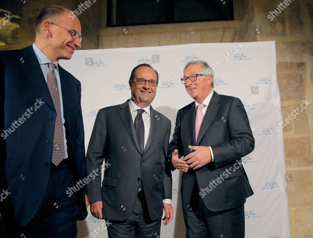 Stock Photo of Former Italian Prime Minister Enrico Letta, left, French President Francois Hollande, center, and European Commission President Jean-Claude Juncker, talk together after a group photo during an event for the 20th anniversary of the Jacques Delors institute in Paris