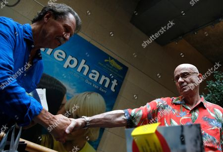 U.S author James Ellroy shakes hands with a man during a signing session in Paris