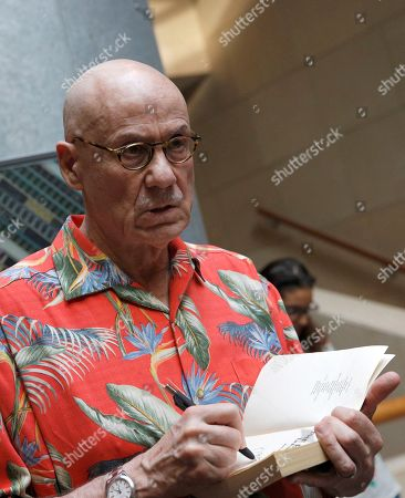U.S author James Ellroy signs a book during a signing session in Paris