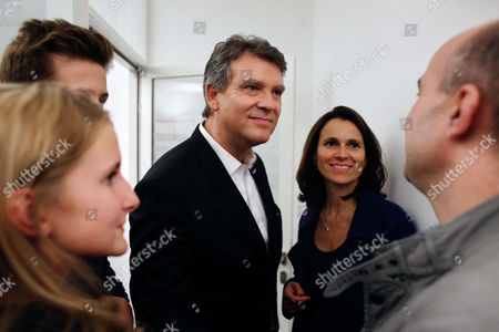 Former French economy minister and candidate Arnaud Montebourg, center, and former French Culture Minister Aurelie Filippetti, second right, talk with a supporter during the inauguration of his campaign headquarters for the 2017 presidential election, in Paris