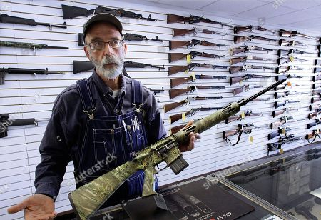 Steve Swartz, owner of Capitol City Arms Supply, shows off a semi-automatic rifle in Springfield, Ill., . Guns are selling like hotcakes in Illinois, with sales jumping nearly 40 percent in November alone, a trend many attribute to concern among gun rights advocates that Democrats empowered by election gains will look to tighten gun control measures