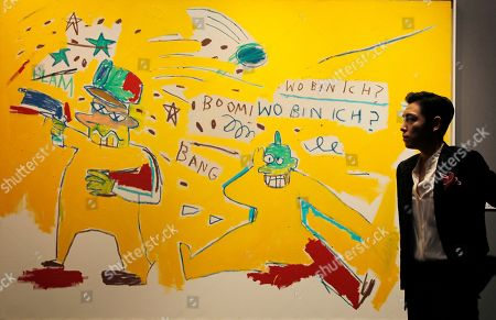 "Choi Seung-hyun, T.O.P Singer and actor Choi Seung-hyun, better known by his stage name T.O.P, of South Korean boy band BIGBANG, poses in front of a painting titled ""Infantry"" by American artist, Jean-Michel Basquiat during a Sotheby's guest-curated contemporary art auction in Hong Kong, China, . The painting which was curated by T.O.P is expected to fetch US$3,850-5,130,000"