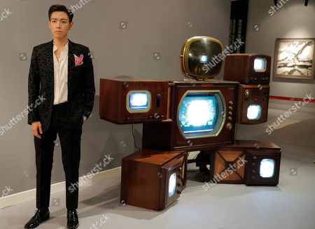 "Stock Picture of Choi Seung-hyun, T.O.P Singer and actor Choi Seung-hyun, better known by his stage name T.O.P, of South Korean boy band BIGBANG, poses in front of an art installation titled ""Fat Boy"" by Korean American artist Nam June Paik during a Sotheby's guest-curated contemporary art auction in Hong Kong, China, . The installation which was curated by T.O.P is expected to fetch US$449,000-577,500"