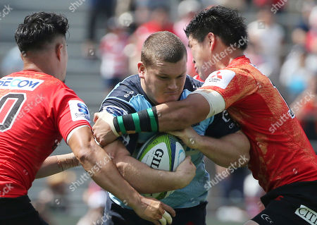Waratahs Tom Robertson is tackled by Sunwolves Yu Tamura, left, and Harumichi Tatekawa, right, during their Super Rugby match in Tokyo, Japan, Saturday, July 2, 2016.