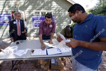 Shahul Feroze, Ali Chaudry, Shawn Butt In Basking Ridge, N.J., Shahul Feroze, right, of South Brunswick, N.J., gets information about voter registration from Dr. Ali Chaudry, left, of Basking Ridge, N.J., and Shawn Butt, of Piscataway, N.J., during a voter registration drive following a prayer service at the Bernards Township Community Center. The case of the New Jersey Muslim charged with planting bombs in New York and New Jersey is the latest of many challenging moments for the state's large Muslim population. They have been a target of anti-Muslim rhetoric in the presidential campaign and have seen their governor, once considered a strong ally, endorse a presidential candidate who has thrown suspicion on their entire community