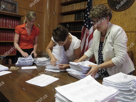 Beth Herzog, left, a public information officer for North Dakota Secretary of State Al Jaeger, Lee Ann Oliver, center, Jaeger's elections director, and Jaeger's administrative assistant, Kim Shaw, right, count citizen initiative petitions in the secretary of state's office in the North Dakota Capitol in Bismarck, N.D., on . The petitions, which were delivered Monday, ask for a statewide vote on a proposed law that would make it legal for North Dakotans to use marijuana for pain relief