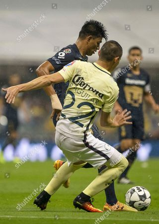 Stock Picture of Jesus Vasconcelos, Paul Aguilar Pumas' Jesus Gallardo, left, fights for the ball with America's Paul Aguilar during a Mexican soccer league match in Mexico City