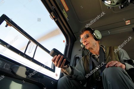 """Robert Bewley checks the flight path of a helicopter piloted by Jordanian air force to GPS coordinates of archaeological sites in Jordan. For the past 19 years, Bewley and colleague David Kennedy have flown above Jordan to photograph, discover and preserve archaeology. Photographing from helicopters dozens of Roman, Ottoman, Byzantine, Nabatean, Neolithic and British imperial sites, the pair have made two major discoveries: mysterious man-made rock structures in Jordan's deep desert and """"catastrophic"""" urban sprawl destroying and threatening sites across the kingdom"""