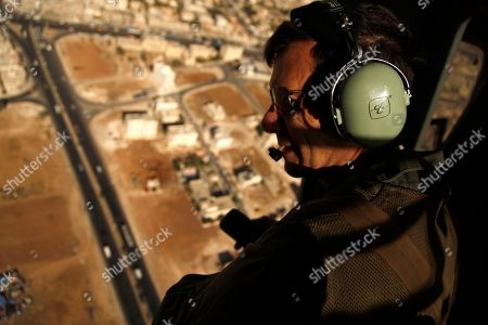 """Robert Bewley uses his radio headset to guide helicopter pilots from the Jordanian air force to an archaeological site in Jordan. Bewley and his colleague David Kennedy have spent the past 19 years in an ongoing project documenting from the air archaeological sites around Jordan. Since, they've revealed from the air mysterious rock structures in the bleak eastern desert ? and witnessed """"catastrophic"""" urban sprawl destroying and threatening sites across the kingdom"""