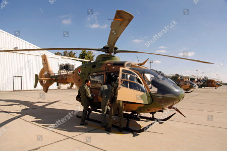 """Jordanian air force helicopter pilots and archaeologist Robert Bewley ready a helicopter for a mission to photograph archaeological sites in Jordan. Bewley and colleague David Kennedy have flown above Jordan to photograph, discover and preserve archaeology. Photographing from helicopters dozens of Roman, Ottoman, Byzantine, Nabatean, Neolithic and British imperial sites, the pair have made two major discoveries: mysterious man-made rock structures in Jordan's deep desert and """"catastrophic"""" urban sprawl destroying and threatening sites across the kingdom"""