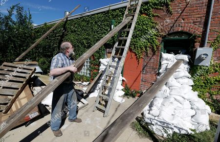 Michael Richards moves pieces of wood to the roof of his building, in Cedar Rapids, Iowa. Residents of Cedar Rapids are waiting anxiously as the quickly rising Cedar River threatens to inundate their city with devastating floodwaters for the second time in eight years