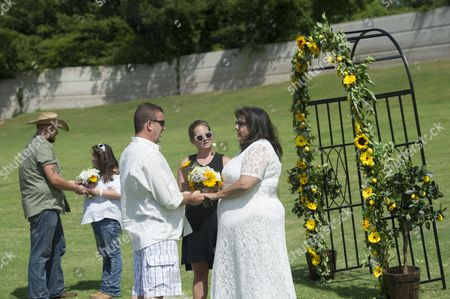 IMAGE DISTRIBUTED FOR MIKE'S HARD LEMONADE - Country music fans and real-life couples Nikki and Joseph Walsh, left, and Lisa Taylor and Jerry Drozdiel, right, tie the knot in an unconventional backyard wedding, hosted by mike's hard lemonade, before the start of the Randy Houser concert at the Lakewood Amphitheatre, Friday, July 15, 2016, in Atlanta.