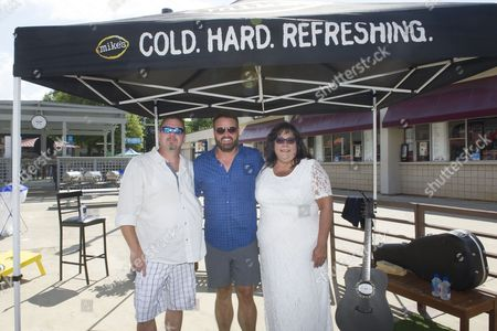 IMAGE DISTRIBUTED FOR MIKE'S HARD LEMONADE - Country music singer and songwriter Randy Houser poses with fans and real-life couple Lisa Taylor and Jerry Drozdiel following a performance for their first dance after tying the knot in a backyard wedding, hosted by mik's hard lemonade, before his concert at the Lakewood Amphitheatre, Friday, July 15, 2016, in Atlanta.