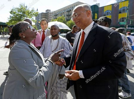 Imam Souleimane Konate, Bill Thompson A passerby, left, stops New York City Democratic Mayoral hopeful Bill Thompson, right, on the street as Thompson campaigned with members of the West African community, including Imam Souleimane Konate, center, of Mali, in the West Harlem neighborhood of New York, . The Democratic primary election is Tuesday, Sept. 10