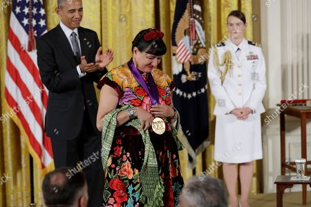 Stock Photo of Barack Obama, Sandra Cisneros Author Sandra Cisneros walks back to her seat after being awarded the 2015 National Medal of Arts by President Barack Obama during a ceremony in the East Room of the White House, in Washington