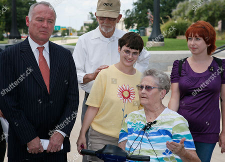 """Carrol Stanley, David Slane, John Stanley, W.M., Amanda Moore Carrol Stanley, second from right, talks to the media along with from left, attorney David Slane, her husband, John Stanley, and her foster child, """"W.M."""" outside the Supreme Court in Oklahoma City, . On behalf of six clients, Slane is suing Oklahoma's governor over $140 million in unspent state dollars that he contends should go to state agencies. At right is Amanda Moore, a volunteer guardian and also a plaintiff"""