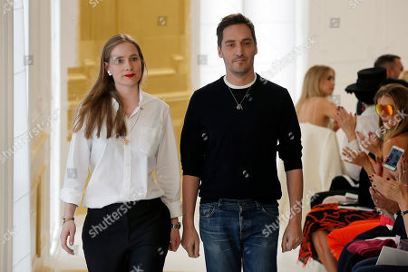 Fashion designers Serge Ruffieux, right, and Lucie Meier acknowledge applause at the end of Christian Dior's Haute Couture Fall-Winter 2016-2017 fashion collection presented Monday, July 4, 2016 in Paris.