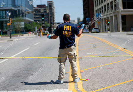 A member of an FBI evidence response team marks the roadway at the scene where one or more gunmen opened fire on Dallas police officers last night in Dallas, Friday, July 8, 2016. A peaceful protest in Dallas over the recent videotaped shootings of black men by police turned violent Thursday night as an unknown number of people shot at officers, killing five and injuring seven, as well as two civilians.