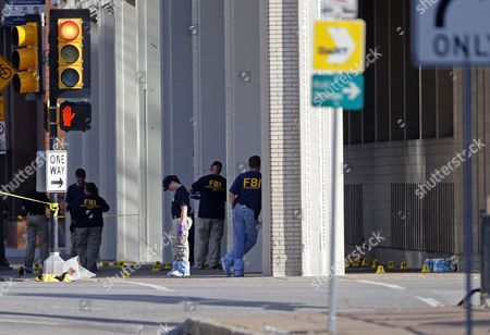 An FBI evidence response team works the scene where one or more gunmen opened fire on Dallas police officers last night in Dallas, Friday, July 8, 2016. A peaceful protest in Dallas over the recent videotaped shootings of black men by police turned violent Thursday night as  gunman Micah Johnson shot at officers, killing five and injuring seven, as well as two civilians.
