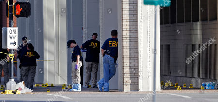 An FBI evidence response team works at the scene of the police shootings in Dallas, Friday, July 8, 2016. Five police officers are dead and several injured following a shooting during what began as a peaceful protest in the city the night before.
