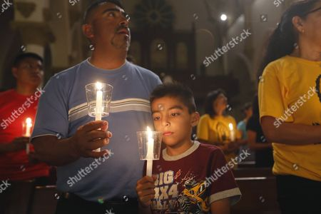 """People participate in a """"United To Heal Prayer Vigil"""" at Cathedral Guadalupe, in honor of the Dallas police officers who were slain Thursday, in Dallas, Friday, July 8, 2016.  A peaceful protest in Dallas over the recent videotaped shootings of black men by police turned violent Thursday night as  gunman Micah Johnson shot at officers, killing five and injuring seven, as well as two civilians."""