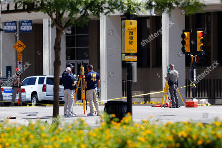 Local and federal investigators work the scene where one or more gunmen opened fire on Dallas police officers last night in Dallas, Friday, July 8, 2016. A peaceful protest in Dallas over the recent videotaped shootings of black men by police turned violent Thursday night as an unknown number of people shot at officers, killing five and injuring seven, as well as two civilians.