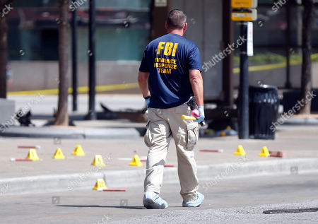 An FBI evidence response team member walks near evidence markers at the scene where one or more gunmen opened fire on Dallas police officers last night in Dallas, Friday, July 8, 2016. A peaceful protest in Dallas over the recent videotaped shootings of black men by police turned violent Thursday night as an unknown number of people shot at officers, killing five and injuring seven, as well as two civilians.