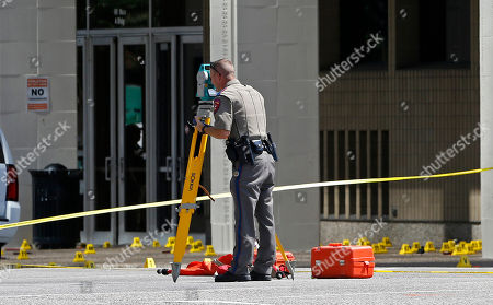 A law enforcement officer works the scene where one or more gunmen opened fire on Dallas police officers last night in Dallas, Friday, July 8, 2016. A peaceful protest in Dallas over the recent videotaped shootings of black men by police turned violent Thursday night as an unknown number of people shot at officers, killing five and injuring seven, as well as two civilians.
