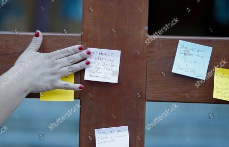 """A parishioner places a prayer to a crucifix before entering a """"United To Heal Prayer Vigil"""" at Cathedral Guadalupe, in honor of the Dallas police officers who were slain Thursday, in Dallas, Friday, July 8, 2016. A peaceful protest in Dallas over the recent videotaped shootings of black men by police turned violent Thursday night as gunman Micah Johnson shot at officers, killing five and injuring seven, as well as two civilians."""
