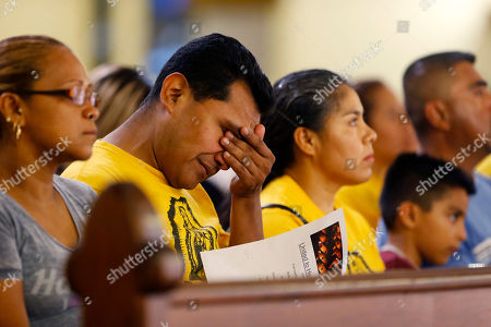 """A worshiper wipes his eyes during a """"United To Heal Prayer Vigil"""" at Cathedral Guadalupe, in honor of the Dallas police officers who were slain Thursday, in Dallas, Friday, July 8, 2016. A peaceful protest in Dallas over the recent videotaped shootings of black men by police turned violent Thursday night as gunman Micah Johnson shot at officers, killing five and injuring seven, as well as two civilians."""