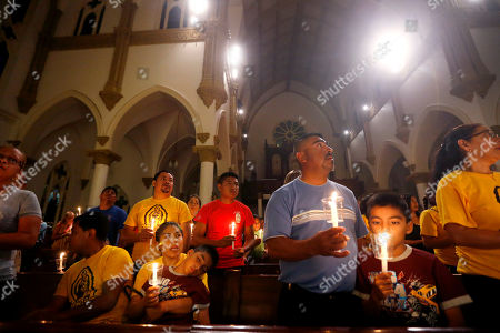 """Worshipers participate in a """"United To Heal Prayer Vigil"""" at Cathedral Guadalupe, in honor of the Dallas police officers who were slain Thursday, in Dallas, Friday, July 8, 2016. A peaceful protest in Dallas over the recent videotaped shootings of black men by police turned violent Thursday night as gunman Micah Johnson shot at officers, killing five and injuring seven, as well as two civilians."""