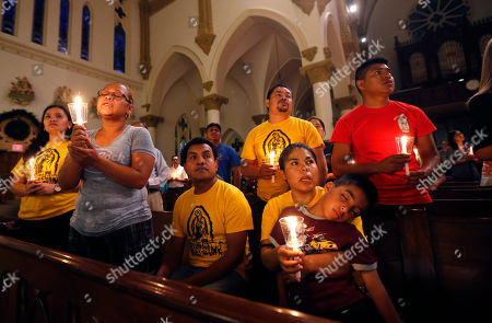 """Worshipers pray and sing during a """"United To Heal Prayer Vigil"""" at Cathedral Guadalupe, in honor of the Dallas police officers who were slain Thursday, in Dallas, Friday, July 8, 2016. A peaceful protest in Dallas over the recent videotaped shootings of black men by police turned violent Thursday night as gunman Micah Johnson shot at officers, killing five and injuring seven, as well as two civilians."""