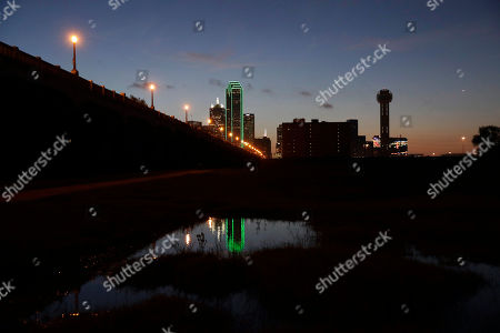 Reunion tower, right, stands with the lights out as the sun rises over downtown Dallas, Friday, July 8, 2016. Many Dallas business turned out their lights to honor the police killed and wounded in an attack Thursday evening.