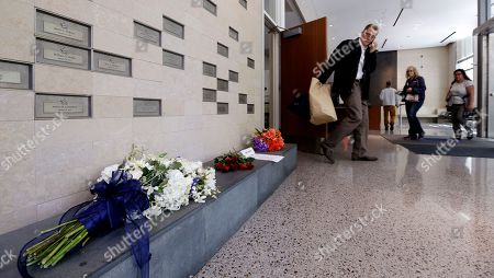 Stock Picture of Flowers are left in the lobby of the Seattle Police Department in reaction to the shootings of police officers in Dallas, Friday, July 8, 2016, in Seattle.