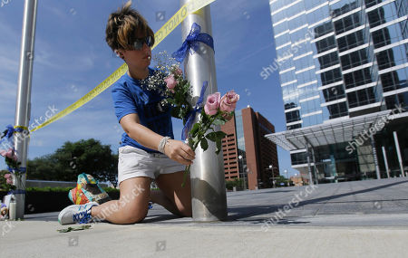 Stock Image of Noelle Hendrix places flowers near the scene of a shooting in downtown Dallas, Friday, July 8, 2016. Snipers opened fire on police officers in the heart of Dallas during protests over two recent fatal police shootings of black men.