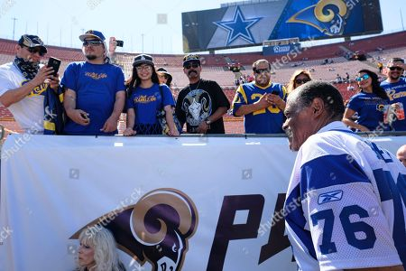 Former Los Angeles Rams' Rosey Grier, right, is greeted by fans as they arrive at Los Angeles Memorial Coliseum on . Los Angeles fans celebrate the return of the NFL and their  long-lost Rams to the city at the team's first preseason NFL game against the Dallas Cowboys