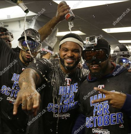 Prince Fielder, center, and his Texas Rangers teammates celebrate after clinching the American League Western Division after a baseball game against the Oakland Athletics, in Oakland, Calif