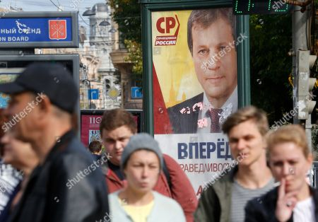 People walk past an election poster of Just Russia party's candidate Alexei Kovalev in St. Petersburg, Russia, . Russia's parliamentary election will be held on Sunday