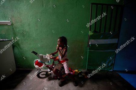 In this June 4, 2016 photo, Alexa Vega eats a piece of bread at her home in the Petare shantytown in Caracas, Venezuela. Vega's mother Kelly moved to Venezuela from Barranquilla, Colombia 12 years ago, attracted by the dazzling boom of the oil country, but now their lives have been hit by runaway inflation and a severe food shortage. Some are turning to urban farming to get vegetables back into their diets.