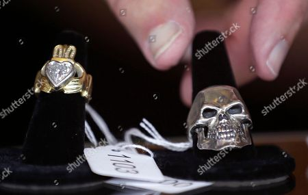 "Auctioneer Bob Sheehan reaches for a silver skull ring, which is on display next to a diamond claddagh ring, that are among items belonging to James ""Whitey"" Bulger and Catherine Greig, which will be auctioned off this weekend at the Boston Convention Center, Friday, June 24, 2016, in Boston. The proceeds will be divided among the families of Bulger's victims."