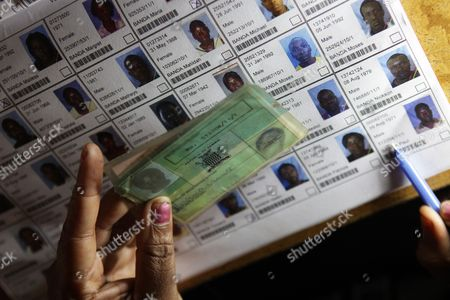 An election official verifies the particulars of a person on the electoral roll during presidential election day in Lusaka, . Zambians are voting to choose a new leader following the death of Michael Sata, 77, who died Oct. 2014, in a London hospital following a long illness, after serving as President of the Southern African country since 2011