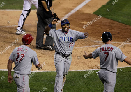 Stock Image of National League outfielder Marlon Byrd, of the Chicago Cubs, center, is greeted at home by teammates National League third baseman Scott Rolen, of the Cincinnati Reds, left, and National League outfielder Matt Holliday, of the St. Louis Cardinals in the seventh inning of the All-Star baseball game, in Anaheim, Calif
