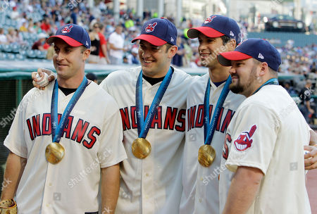Members of the gold medal winning USA bobsled team pose for a photo before throwing out ceremonial pitches before a baseball game between the Oakland Athletics and Cleveland Indians, in Cleveland. From left: Curt Tomasevicz, Justin Olsen, Steve Mesler and Steve Holcomb