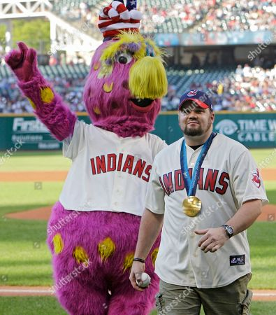 Steve Holcomb, right, driver of the gold-meal winning USA Olympic bobsled team, walks off the field with Cleveland Indians mascot, Slider, after throwing out a ceremonial pitch before a baseball game between the Indians and Oakland Athletics, in Cleveland