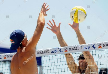 Todd Rogers, right, spikes the ball past John Hyden in the men's beach volleyball final at the AVP Nivea Tour Long Beach Open, in Long Beach, Calif. Rogers, with partner Phil Dalhausser, won against Sean Scott and John Hyden in three games
