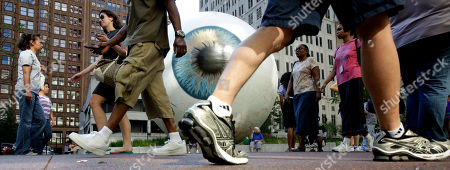 "Stock Picture of Pedestrians walk past Tony Tasset's 30-foot painted fiberglass sculpture ""EYE"" at Pritzker Park inside Chicago's famed loop . The sculpture can be seen until the end of October"