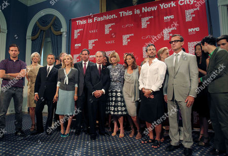 Fashion designers and fashion industry notables pose with New York City Mayor Michael Bloomberg, center, hands clasped, at City Hall in New York, . They were there to promote Fashion's Night Out, an event on Sept. 10, when participating stores will stay open late and offer special promotions and events. Visible, from left, are Jack McCollough partner in Proenza Schouler; Linda Fargo of Bergdorf Goodman; Francisco Costa designer for Calvin Klein; Tory Burch; Saks Chief Executive Officer Stephen Sadove, to left of mayor; Bloomberg; Tracy Reese, behind and right of mayor; Vogue Editor in Chief Anna Wintour; Donna Karan; Marc Jacobs; Carolina Herrera, head turned; CFDA Executive Director Steven Kolb; Vera Wang; Zac Posen and Lazaro Hernandez, Proenza Schouler co-partner